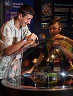 Junior National Young Leaders Conference students interacting with the engaging exhibits at Maryland Science Center